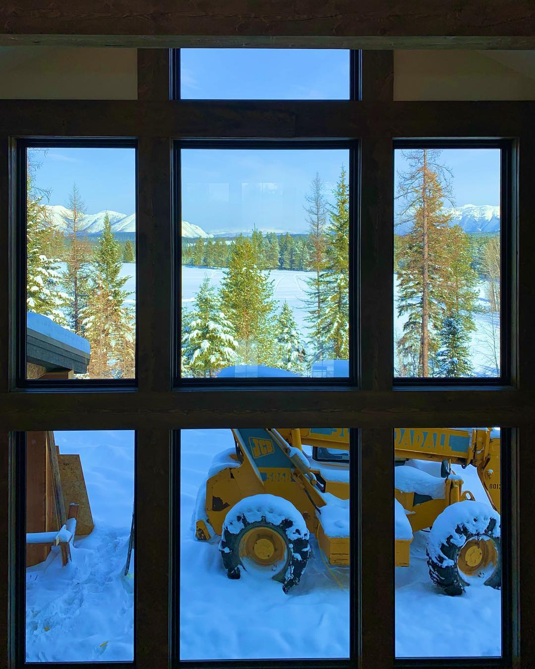 Window wall...minus the big yellow object...this view is perfection! whitefish custom home builder