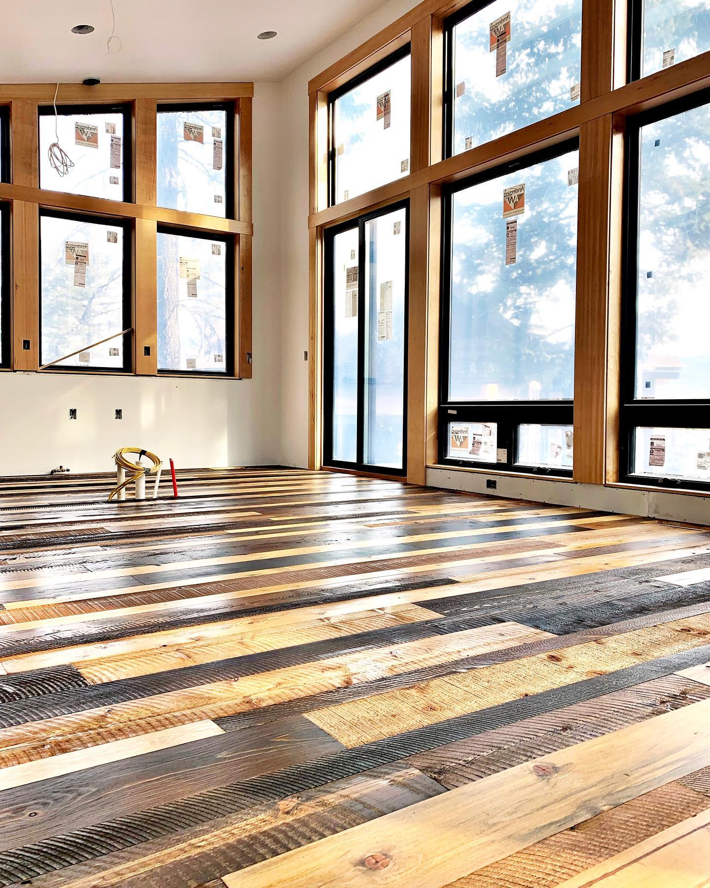 Another Lookout floor nearing completion. This look was created by collecting random widths, textures and species left over from various projects, pre staining different colors and...imitation reclaimed floor accomplished! whitefish custom home builder
